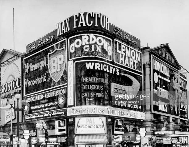 The corner of Piccadilly Circus Westminster London c1961 covered in neon advertising hoardings including BP Gordon's Gin Max Factor and Wrigley's...