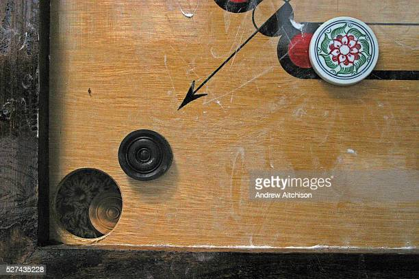 The corner pocket of a carom board during a game Players have to strike the coins into the pockets using the 'striker'