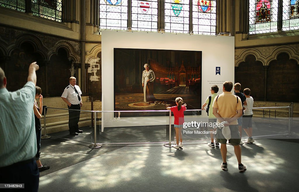 Portrait of Her Majesty Queen Elizabeth II by Ralph Heimans goes back on display in the Chapter House at Westminster Abbey on July 15, 2013 in London, England. An enlarged security barrier and a guard are now in place after the painting was vandalised last month.