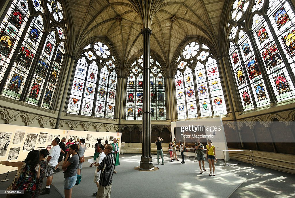 Portrait of Her Majesty Queen Elizabeth II by Ralph Heimans (R) goes back on display in the Chapter House at Westminster Abbey on July 15, 2013 in London, England. An enlarged security barrier and a guard are now in place after the painting was vandalised last month.