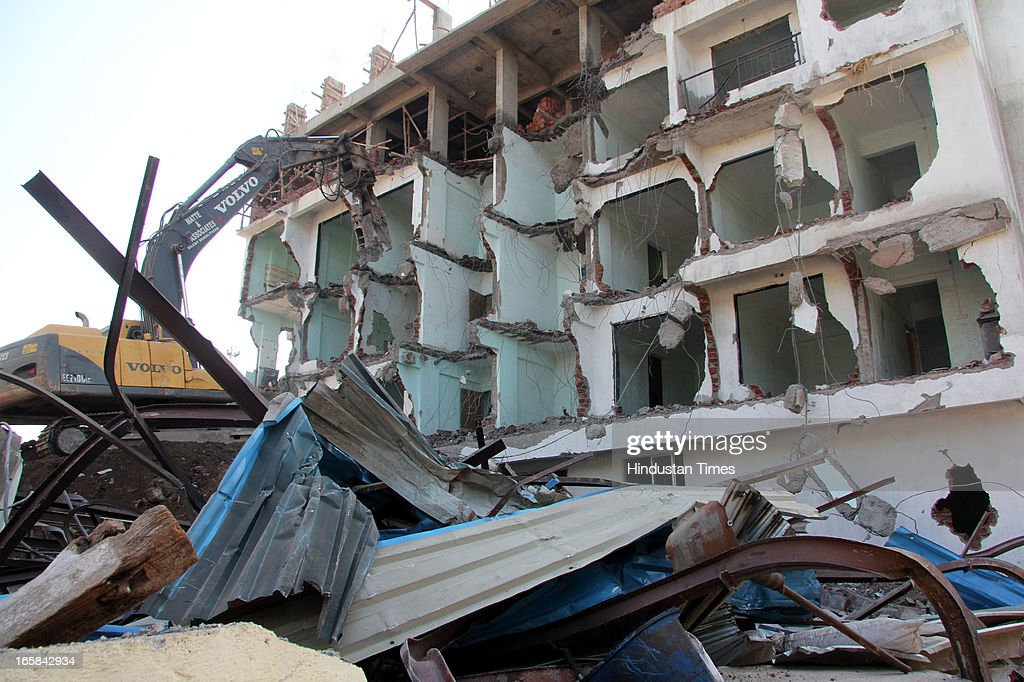 The corporation pulling down the two other buildings in the same compound as of 7-storey illegal structure that caved in here claiming 72 lives on on April 6, 2013 in Thane, India. Rescue operations were called off after 62 people were pulled out of the debris.