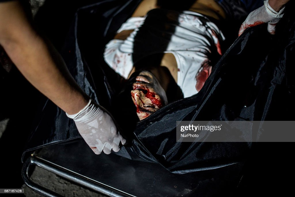 Image depicts graphic content The corpse of a suspected drug pusher and victim of a vigilantestyle execution is placed in a body bag after he was...