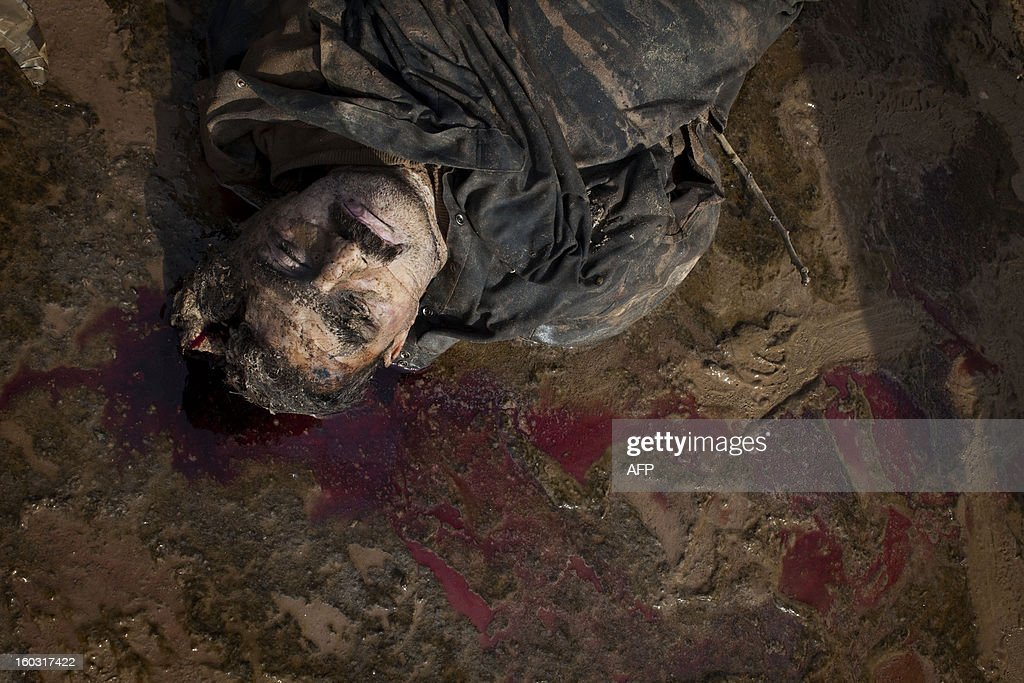 The corpse of an executed man lies on the side of a canal in the northern Syrian city of Aleppo on January 29, 2013. The bodies of at least 68 unidentified young men and boys, all executed with a single gunshot to the head or neck, were found in the Quweiq River, which separates the Bustan al-Qasr district from Ansari in the southwest of the northern city, in a rebel-held area where a Free Syrian Army captain said that many more were still being dragged from the water.