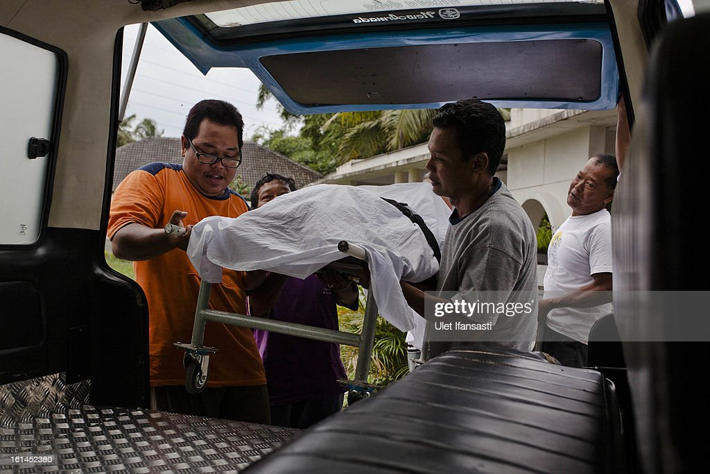 The corpse of Italian artist Andrea Giovanni Sorteni, 48, is loaded into an ambulance as it is taken to a funeral home from Sleman District Hospital on February 11, 2013 in Yogyakarta, Indonesia. Giovanni allegedly died from acute and severe dehydration. He has been arrested on the resort island of Bali for allegedly making a hoax bomb threat to a flight after his wife failed to get a seat.