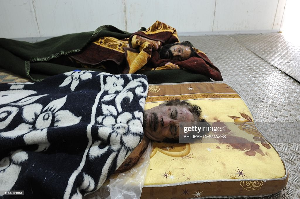 The corpses of Libya's ex-strongman Moamer Kadhafi (R) and his son Mutassem are pictured on mattresses inside the cold storage room of a vegetable market near a mosque on the outskirts of Misrata on October 22, 2011. Military commanders in the Libyan city of Misrata said that no post-mortem would be carried out on the body of Kadhafi despite concerns over how the toppled dictator died. AFP PHOTO/PHILIPPE DESMAZES