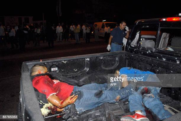 The corpses of two policemen killed with two others comrades remain inside a pickup truck on November 19 in Culiacan Sinaloa state northern Mexico...