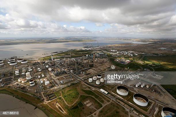 The Coryton oil refinery sits inactive as shipping cranes stand on the shoreline beyond at DP World Ltd's London Gateway deepsea port in this aerial...