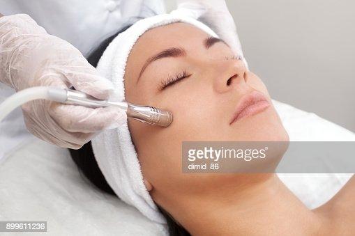 美容師は、美容サロンでプロシージャ マイクロダーマブレーション美しい、若い女性の顔の皮膚のようになります : ストックフォト