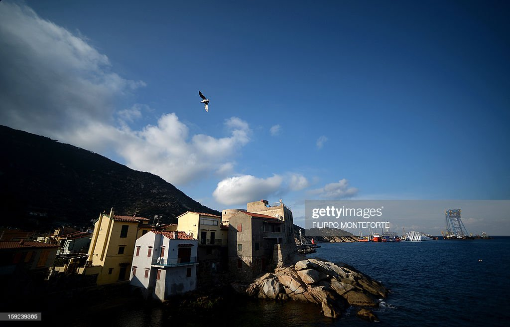 The Costa Concordia cruise ship is seen from the village as it lays aground on January 10, 2013 on the Italian island of Giglio. A year on from the Costa Concordia tragedy in which 32 people lost their lives, the giant cruise ship still lies keeled over on an Italian island and its captain Francesco Schettino has become a global figure of mockery. AFP PHOTO / FILIPPO MONTEFORTE