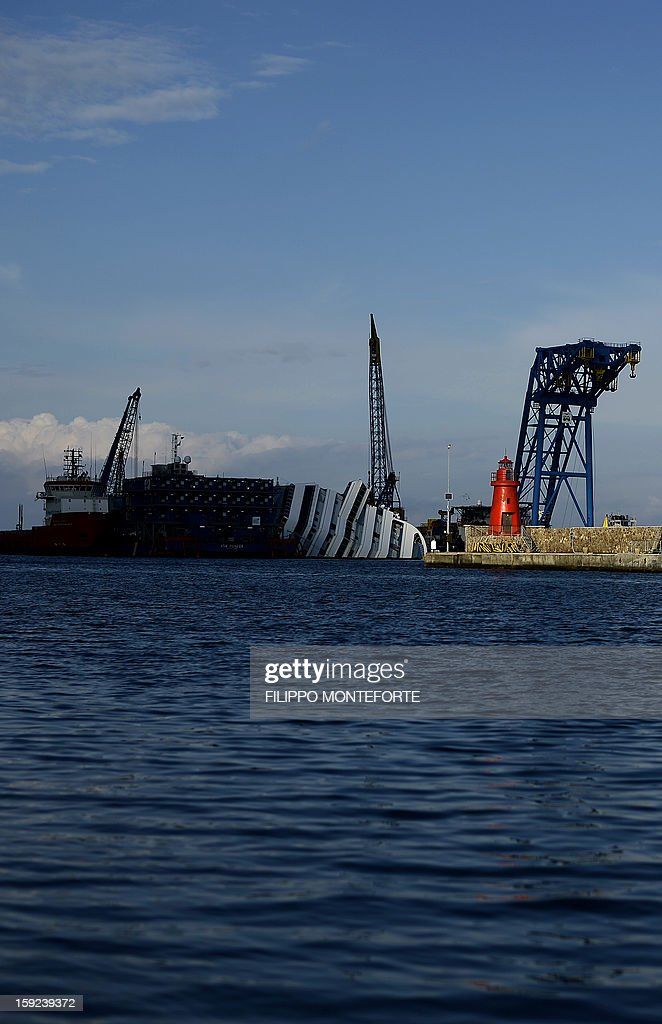 The Costa Concordia cruise ship is seen from the village as it lays aground on January 10, 2013 on the Italian island of Giglio. A year on from the Costa Concordia tragedy in which 32 people lost their lives, the giant cruise ship still lies keeled over on an Italian island and its captain Francesco Schettino has become a global figure of mockery.
