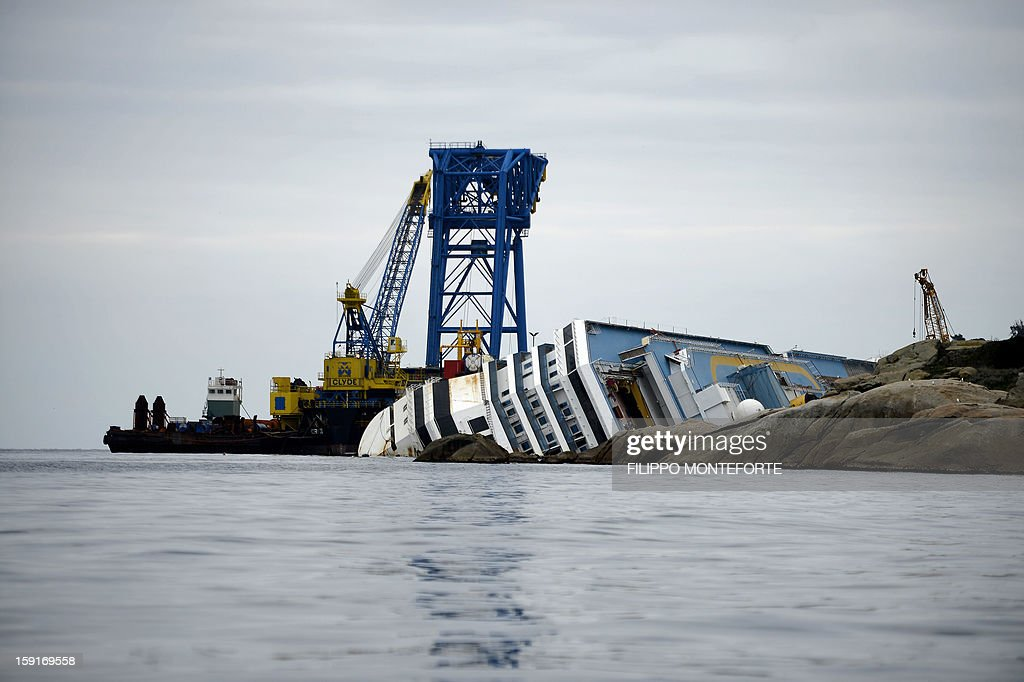The Costa Concordia cruise ship lays aground near the port on January 9, 2013 on the Italian island of Giglio. A year on from the Costa Concordia tragedy in which 32 people lost their lives, the giant cruise ship still lies keeled over on an Italian island and its captain Francesco Schettino has become a global figure of mockery. AFP PHOTO / FILIPPO MONTEFORTE
