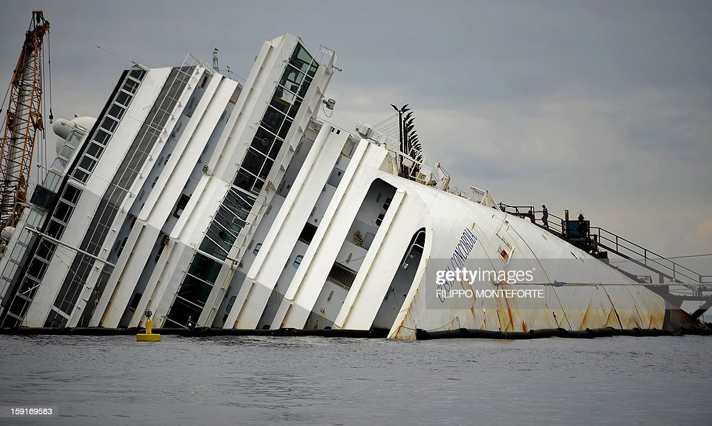 The Costa Concordia cruise ship lays aground near the port on January 9, 2013 on the Italian island of Giglio. A year on from the Costa Concordia tragedy in which 32 people lost their lives, the giant cruise ship still lies keeled over on an Italian island and its captain Francesco Schettino has become a global figure of mockery.