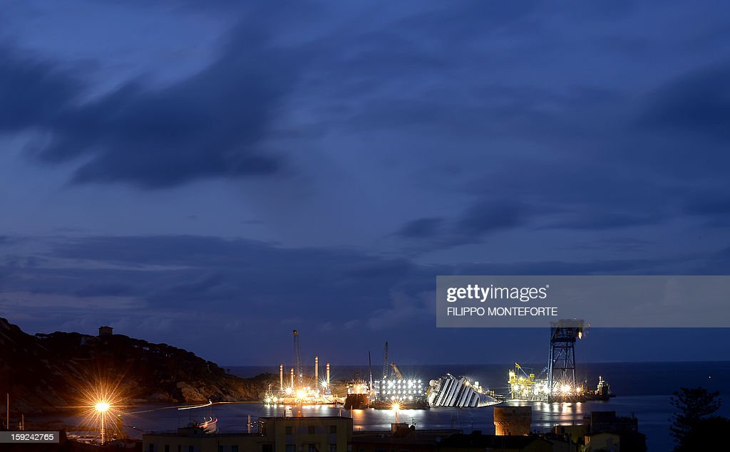 The Costa Concordia cruise ship lays aground near the port on January 10, 2013 on the Italian island of Giglio. A year on from the Costa Concordia tragedy in which 32 people lost their lives, the giant cruise ship still lies keeled over on an Italian island and its captain Francesco Schettino has become a global figure of mockery. AFP PHOTO / FILIPPO MONTEFORTE