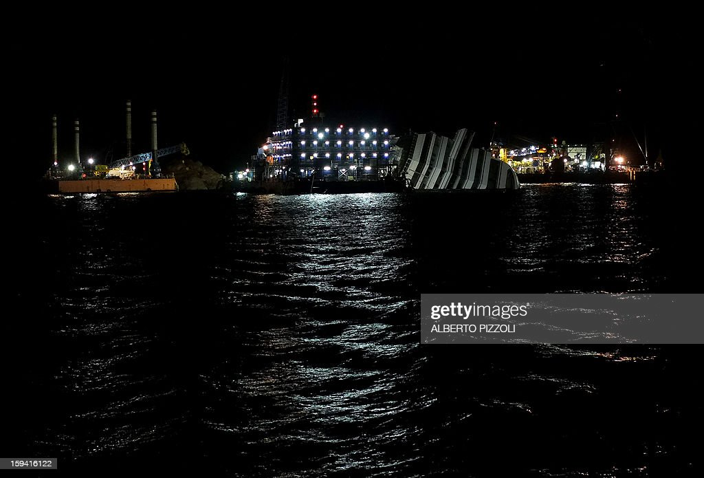 The Costa Concordia cruise ship lays aground on January 13, 2013 on the Italian island of Giglio. Survivors, grieving relatives and locals on the island of Giglio gathered on January 13 to mark the first anniversary of the Costa Concordia cruise ship disaster, which claimed 32 victims. AFP PHOTO / ALBERTO PIZZOLI