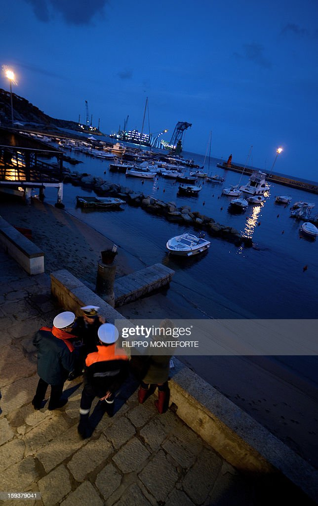 The Costa Concordia cruise ship (background) remains on the shoreline of the Italian island of Giglio on January 12, 2013. Shaken survivors and grieving relatives of the 32 victims of the Costa Concordia cruise ship disaster began arriving on the island of Giglio for a first anniversary commemoration of the tragedy.