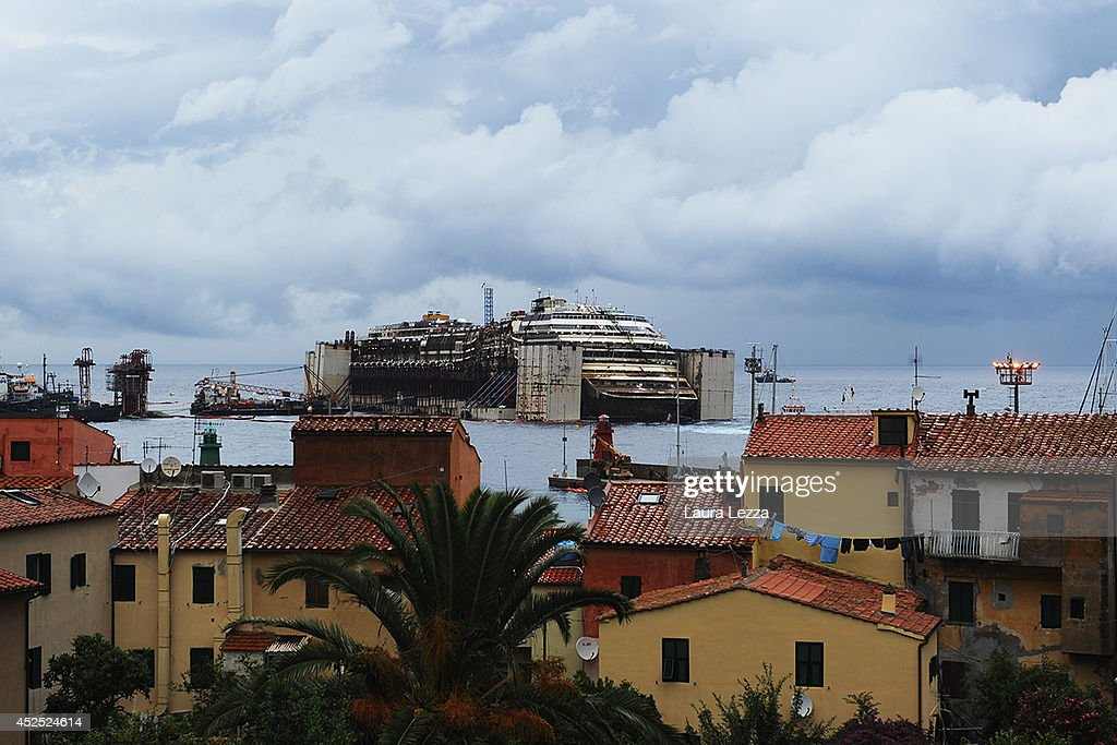 The Costa Concordia is visible from Giglio Porto as it sits in the water during the last stage of refloating operation on July 22, 2014 in Isola del Giglio, Italy. Technicians are working to finish the refloat of the ship and aim to start towing the ship to the port of Genoa for dismantling on Wednesday, July 23.