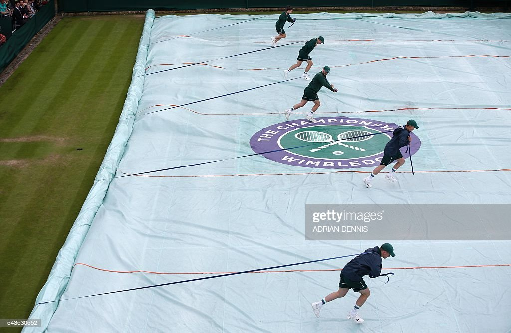 The covers are taken off court 18 as rain delays the start of the third day of the 2016 Wimbledon Championships at The All England Lawn Tennis Club in Wimbledon, southwest London, on June 29, 2016. / AFP / ADRIAN