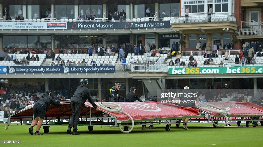 The covers are wheeled on as rain stops play in the fourth One Day International (ODI) cricket match between England and Sri Lanka at The Oval cricket ground in London on June 29, 2016. England captain Eoin Morgan elected to field after winning the toss in the fourth one-day international against Sri Lanka at The Oval on Wednesday. With light rain around and dark grey skies, Morgan clearly felt his bowlers could utilise the favourable bowling conditions with further down pours forecast during the afternoon and evening. ECB