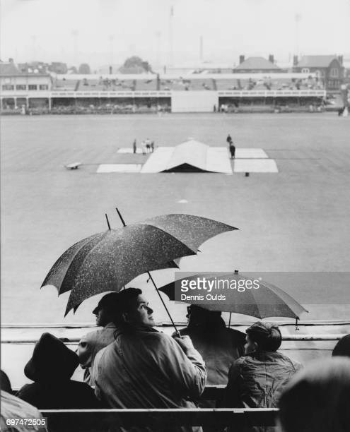 The covers come on to protect the wicket and spectators in the grandstand put up umbrellas as rain delays the start of the third day of the first...