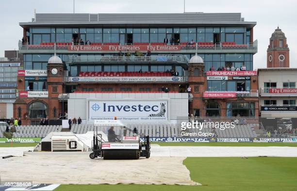 The covers remain on as rain delays the start of day one of 4th Investec Test match between England and India at Old Trafford on August 7 2014 in...