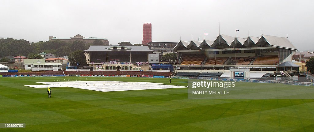 The covers remain on the pitch as rain halts all play during day five of the international cricket Test match between New Zealand and England played at the Basin Reserve in Wellington on March 18, 2013. AFP PHOTO / Marty MELVILLE