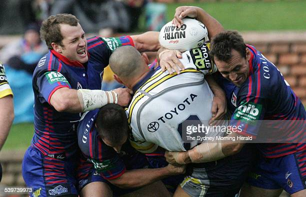 The Cowboys' Paul Rauhihi is tackled by the Knights defence during the NRL rugby league match between the North Queensland Cowboys and Newcastle...