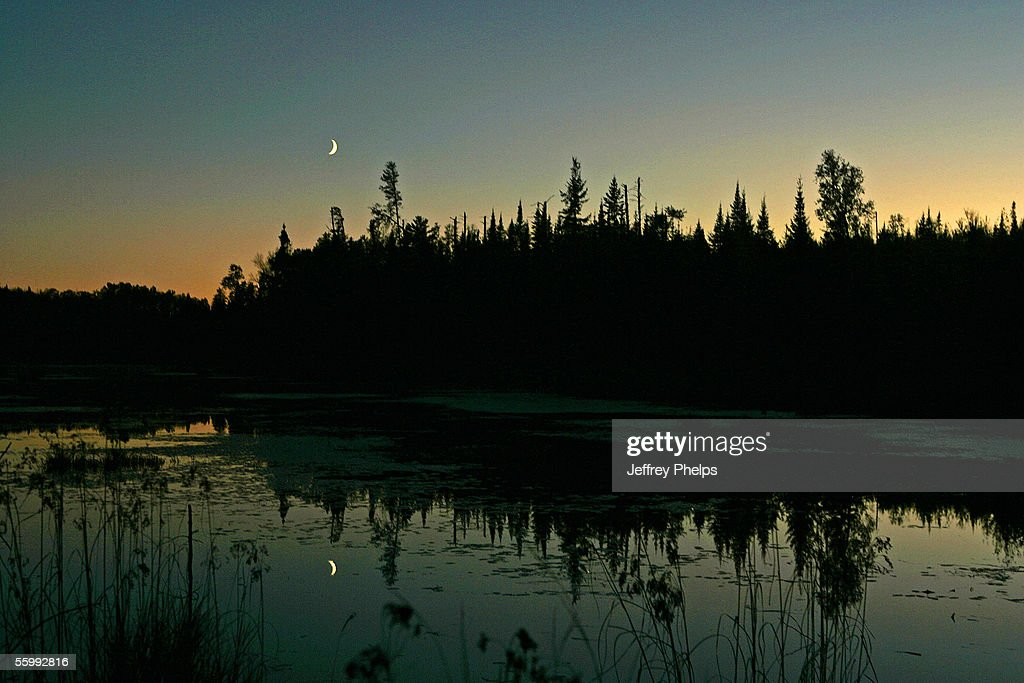 The Cresent Moon is reflected at dusk in a shallow lake along Highway 2 October 8 2005 near Ely Minnesota