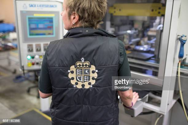 The crest of The Royal Mint sits on the jacket of an employee operating a coin press during the production of gold bullion coins at The Royal Mint in...