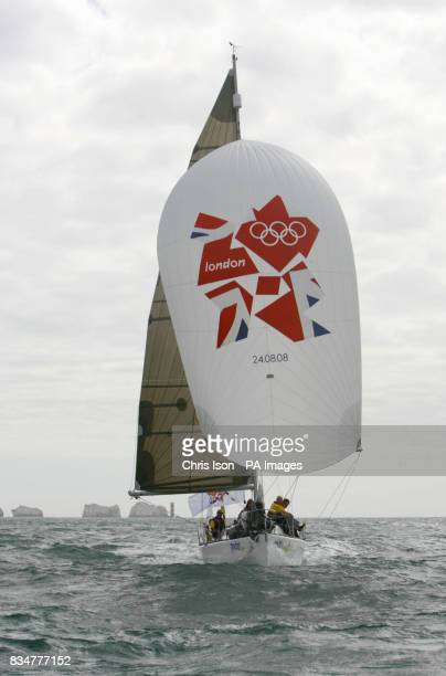 The crew aboard Paddiywack a 32ft Seaquest yacht sail past the Needles lighthouse flying a spinnaker bearing the London 2012 logo as the Olympic...