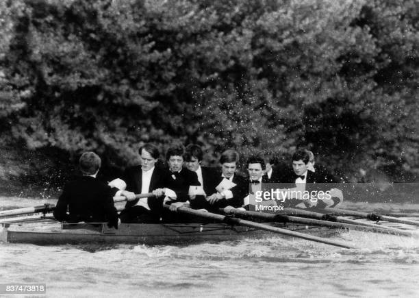 The crew from Oxford row down the thames in their boat dressed in dinner suits and bow ties