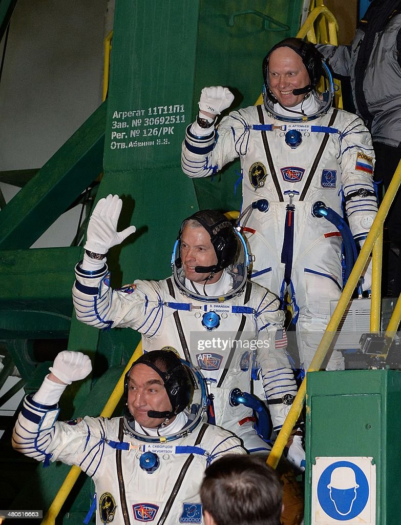 The crew members of a mission to the International Space Station (ISS), US astronaut Steven Swanson (C), Russian cosmonauts Alexander Skvortsov (bottom) and Oleg Artemyev (top) wave as they board their Soyuz-FG rocket with the Soyuz TMA-12M spacecraft at the Russian-leased Baikonur cosmodrome in Kazakhstan, early on March 26, 2014. The launch of the international crew is scheduled early on March 26.