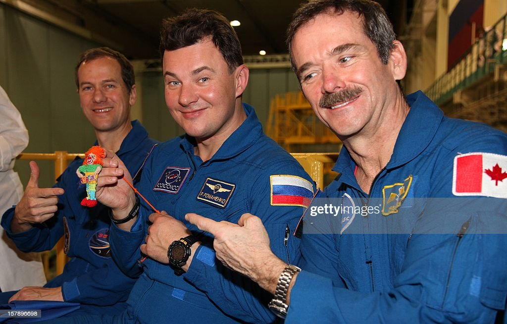 The crew members of the next expedition to the International Space Station (R-L), Canadian astronaut Chris Hadfield, Russian cosmonaut Roman Romanenko and US astronaut Tom Marshburn, show a small toy they will take with them to the ISS during preflight preparation at the Russian leased Kazakhstan's Baikonur cosmodrome on December 7, 2012. Hadfield, Romanenko and Marshburn will join in December the remaining ISS crew, Russians Oleg Novitskiy and Evgeny Tarelkin, and Kevin Ford of the United States, who arrived there last month.