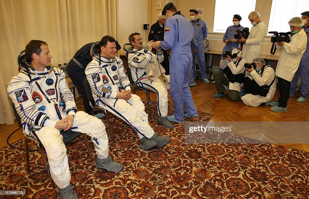 The crew members of the next expedition to the International Space Station (R-L), Canadian astronaut Chris Hadfield, Russian cosmonaut Roman Romanenko and US astronaut Tom Marshburn, put on his space suit during preflight preparation at the Russian leased Kazakhstan's Baikonur cosmodrome on December 7, 2012. Hadfield, Romanenko and Marshburn will join in December the remaining ISS crew, Russians Oleg Novitskiy and Evgeny Tarelkin, and Kevin Ford of the United States, who arrived there last month.