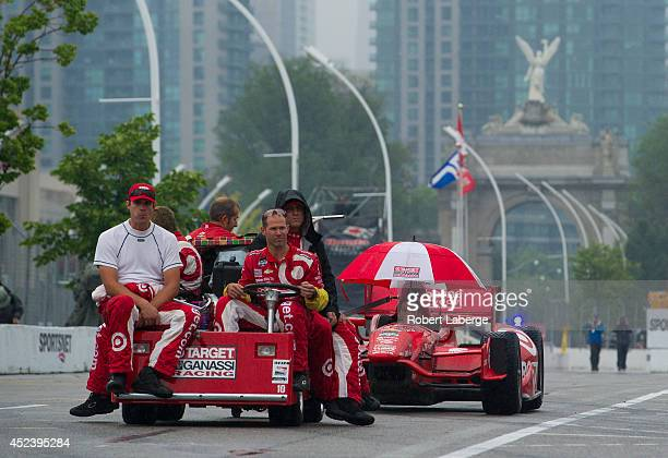 The crew members of the Target Chip Ganassi Racing Dallara Chevrolet of Tony Kanaan of Brazil roll their race car out of the pits after the...
