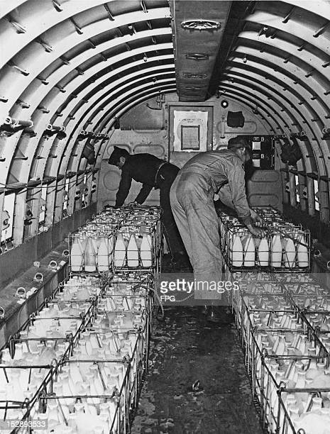 The crew of a Douglas C47 Skytrain load up a cargo of milk in Frankfurt RhineMain part of the Berlin airlift during the Berlin Blockade August 1948...