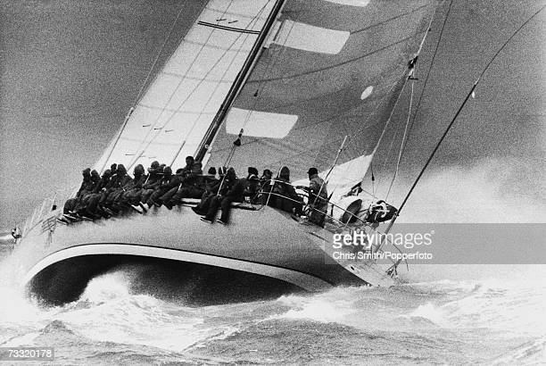 The crew of a racing yacht sitting on the side of the vessel wearing waterproof overalls during stormy weather 1980s