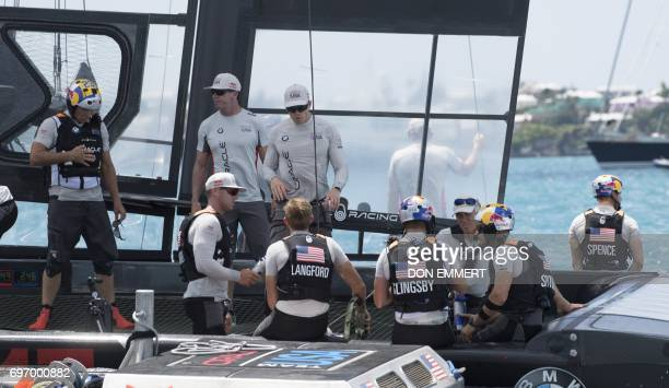 The crew of Oracle Team USA sit on the stern of their boat after losing the first race of the day to Emirates Team New Zealand in the Great Sound...