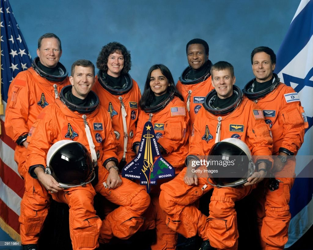 The crew of Space Shuttle Columbia's mission STS-107 take a break from their training regime to pose for the traditional crew portrait. Seated in front are astronauts Rick D. Husband (L), mission commander; Kalpana Chawla, mission specialist; and William C. McCool, pilot. Standing are (L to R) astronauts David M. Brown, Laurel B. Clark, and Michael P. Anderson, all mission specialists; and Ilan Ramon, payload specialist representing the Israeli Space Agency. The Space Shuttle Columbia broke up over Texas during re-entry on February 1, 2003.