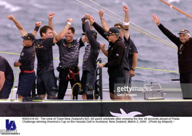 The crew of Team New Zealand's NZL60 yacht celebrate after crossing the line 48 seconds ahead of Prada Challenge winning America's Cup on the Hauraki...