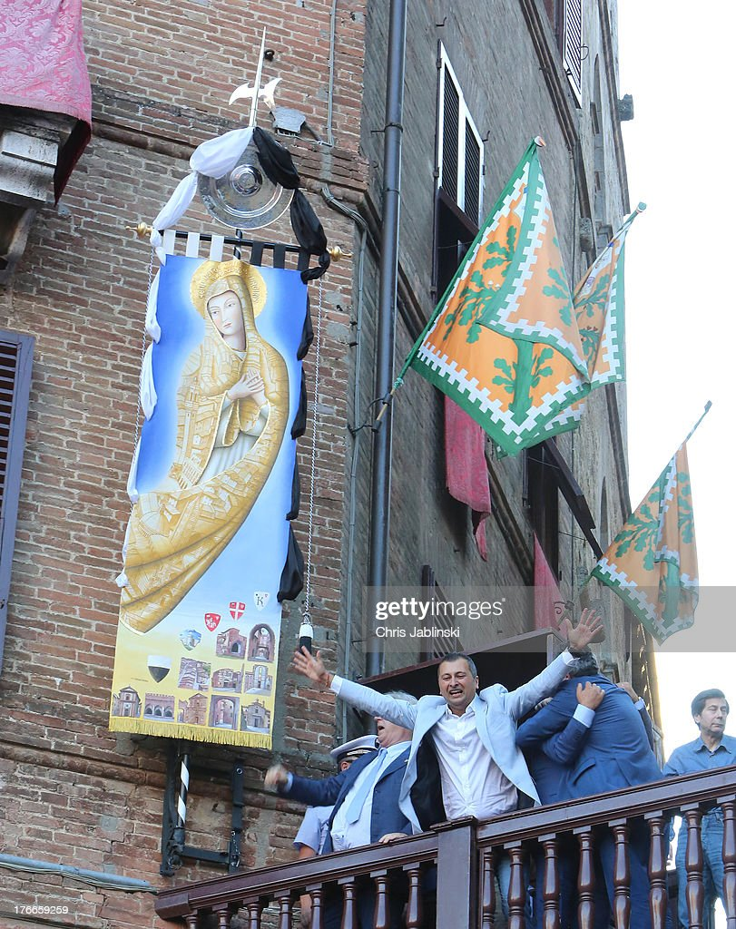 The Crew of the Captain of the Contrada dell`Onda cheers after victory in the annual Palio dell'Assunta horse-race on August 16, 2013 in Siena, Italy. The Palio races in Siena, in which riders representing city districts compete,and takes place twice a year in the summer in a tradition that dates back to 1656.