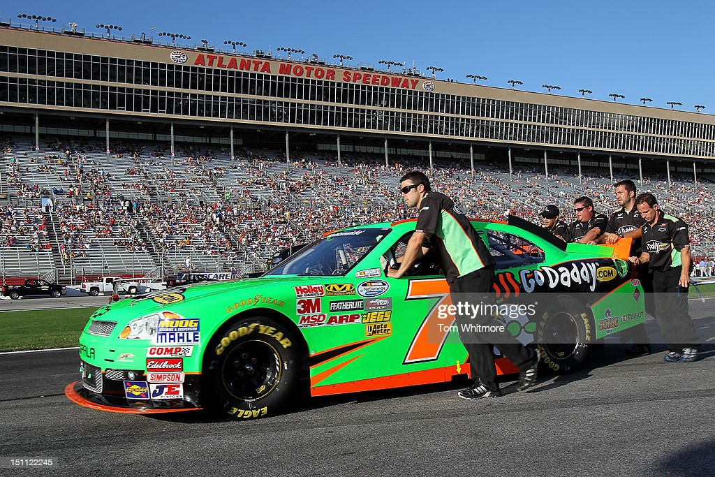 The crew of the #7 godaddy.com Chevrolet driven by Danica Patrick (not pictured) push the #7 car down the grid prior to the start of the NASCAR Nationwide Series NRA American Warrior 300 at Atlanta Motor Speedway on September 1, 2012 in Hampton, Georgia.