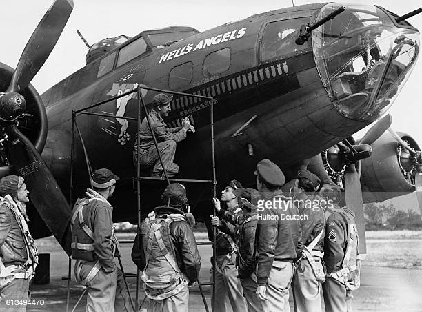 The crew of the Hell's Angel Flying Fortress bomber looks on as Master Sergeant Folmer paints another bomb motif on the aircraft's nose following its...