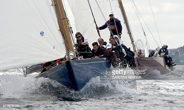 The crew of the racing yacht 'Blue Marlin' steer their boat as they take part in a regatte of the 12mR class on the Baltic Sea on June 20 2015 off...