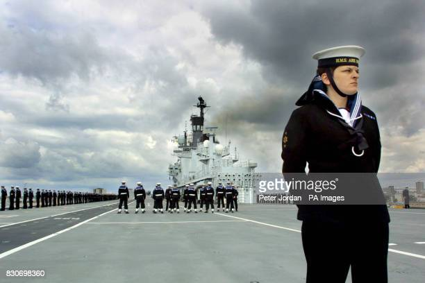The crew of the Royal Navy aircraft carrier HMS Ark Royal stand to attention on the flight deck as she sails into Portsmouth harbour after a two year...