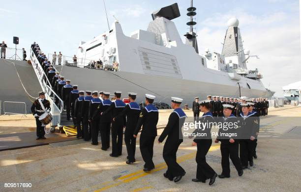 The crew of the Royal Navy's newest warship the Type 45 Destroyer HMS Dragon march aboard as she is handed over to the Royal Navy from the builders...