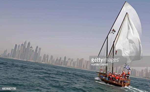 TOPSHOT The crew of Zilzal a dhow captained by Sheikh Hamdan bin Mohammad bin Rashid alMaktoum sails towards the finishing line off the coast of...