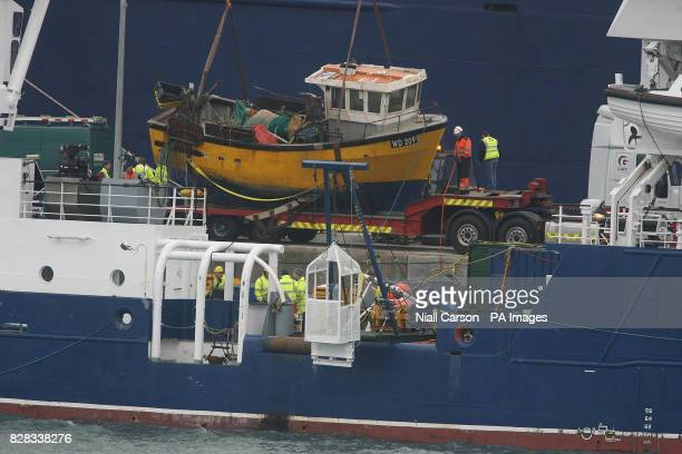 The crew onboard the Granuaile salvage ship Monday February 6 2006 watch the Rising Sun fishing boat as it's lifted onto a low loader in Rosslare...