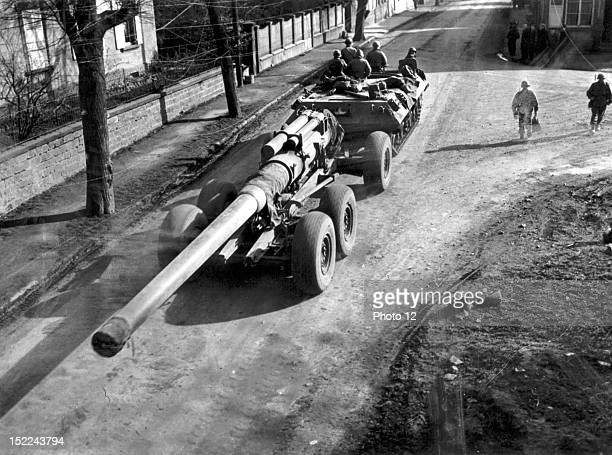 The crew rides atop a tank destroyer towing their 8inch gun through the streets of a French town enroute to the 7th US Army front during the Allied...