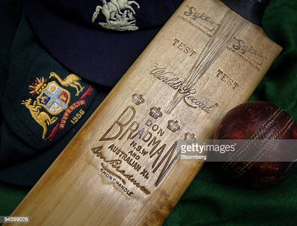The cricket bat which helped Australia's cricket legend Sir Don Bradman score a double century in 1930 is displayed with caps belonging to Dennis...