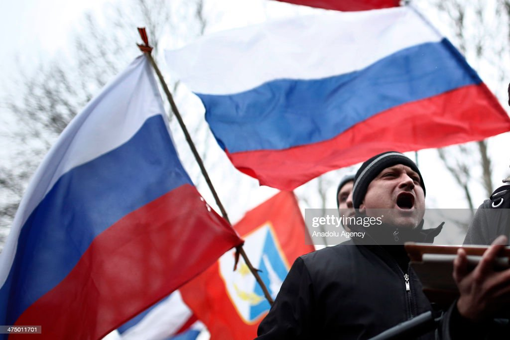 The Crimean people and the supporters of Russia gather in front of the Parliament building in the Autonomous Republic of Crimea's capital Simferopol, Ukraine, on February 26, 2014. The Crimean people shout slogans and hold their flags for the unity of the country at the same time the Russian people shout slogans to support their country.